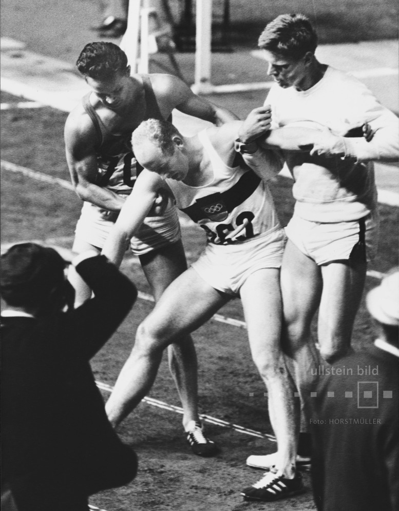Olympische Sommerspiele 1964 in Tokio: Zehnkämper Willi Holdorf bricht nach dem abschließenden 1500-Meter-Lauf vor Erschöpfung zusammen. Er hat die Goldmedaille gewonnen.