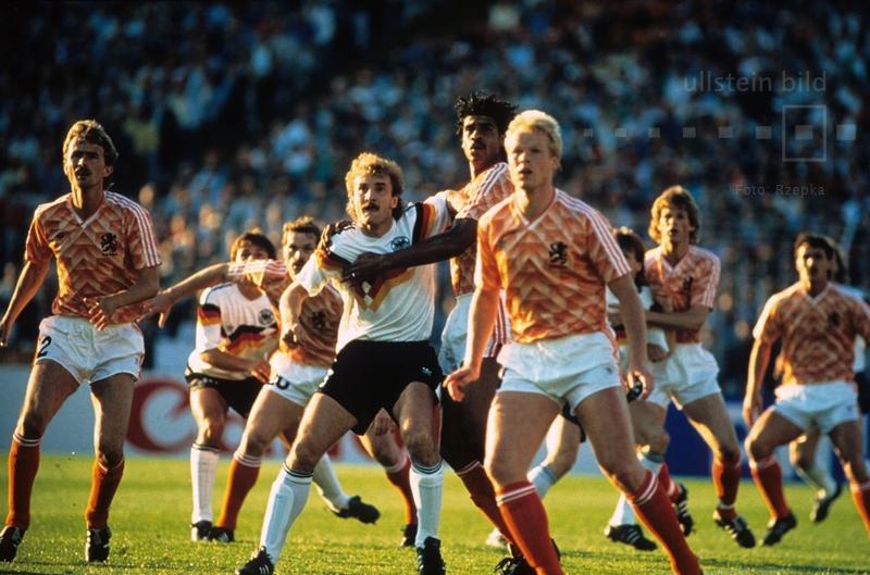 Im EM-Halbfinale 1988 kommt es in Hamburg zum Duell zwischen Gastgeber BR Deutschland und dem Erzrivalen aus Holland. Rudi Völler hat gegen Frank Rijkaard und Ronald Koeman einen schwereren Stand. Die DFB-Auswahl verliert mit 1:2 gegen die Niederlande.