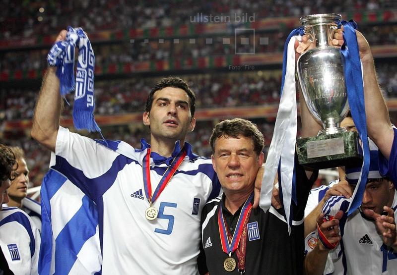 Völlig überraschend gewinnt Griechenland den EM-Titel bei der EURO 2004. Wie bereits im Eröffnungsspiel besiegt Griechenland Gastgeber Portugal, dieses Mal mit 1:0. Otto Rehhagel, der deutsche Nationaltrainer Griechenlands, feiert nach dem Sieg gemeinsam mit Traianos Dellas.