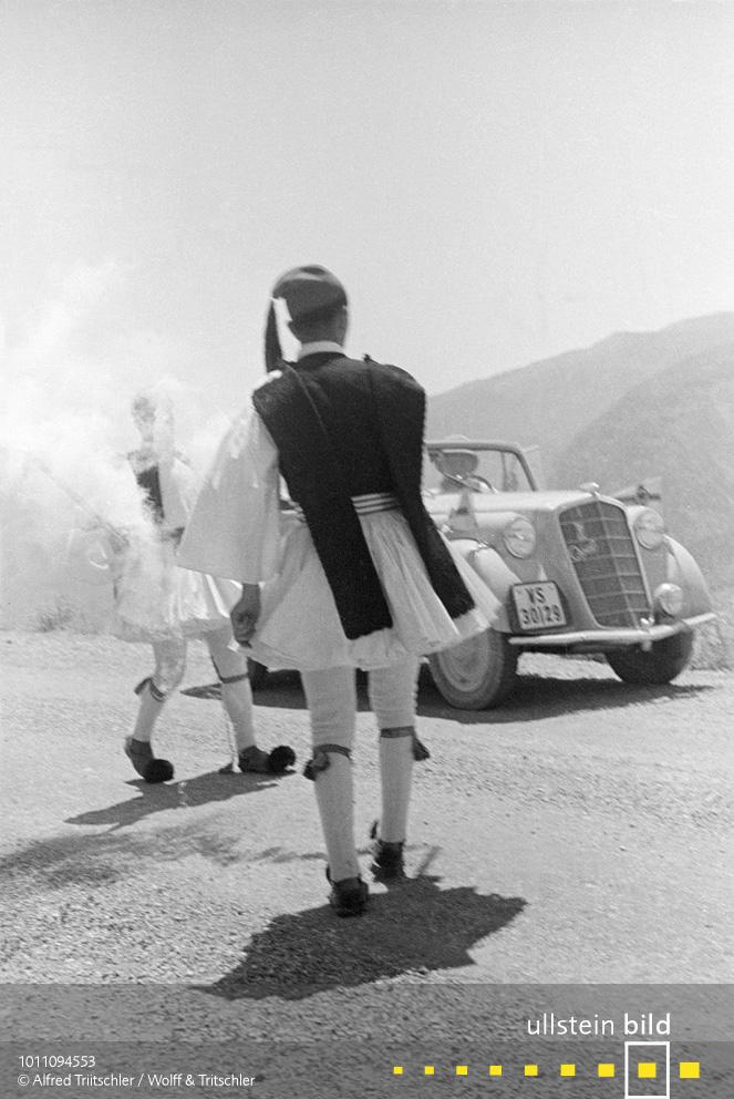 Mit dem Opel Olympia durch Griechenland: Ein griechischer Fackelläufer übergibt auf der Peloponnes das olympische Feuer an einen anderen Fackelläufer - Sommer 1936
