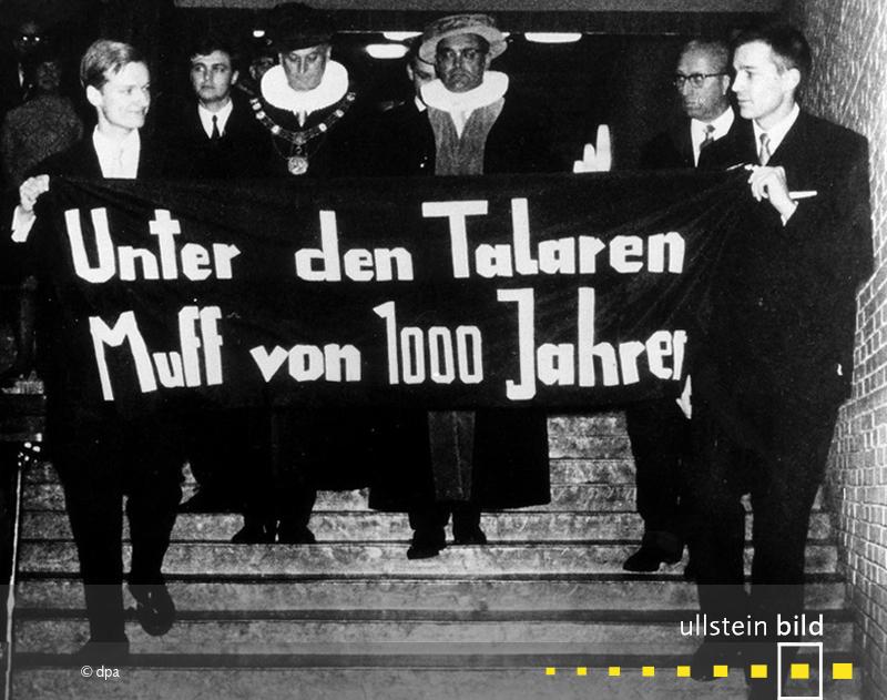 """1967: Bei der Amtseinführung des neuen Rektors der Hamburger Universität entfalten Studenten ein Transparent mit dem Spruch """"Unter den Talaren – Muff von 1000 Jahren""""."""
