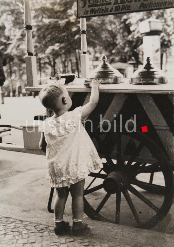 Hitzerekord in Berlin. Kleinkind vor einem Eiswagen auf einer Straße in Berlin. Um 1930. Photographie.