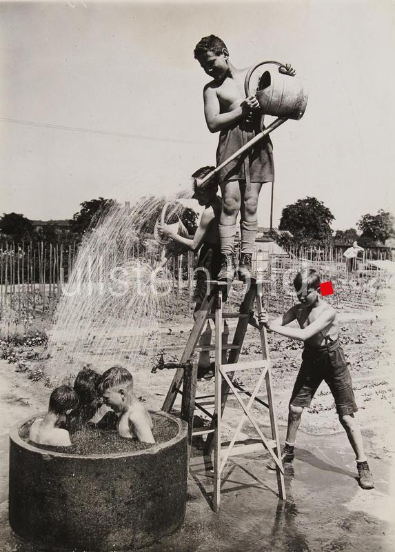 Hitzerekord in Berlin. Improvisiertes Brausebad. Berliner Kinder mit Gießkannen in einer Gartenbauschule. Um 1930.