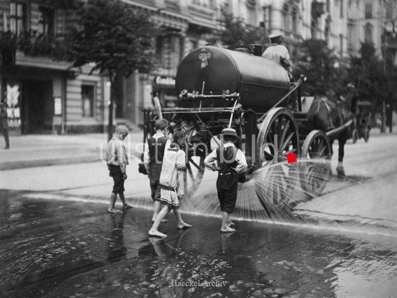 Berliner Strassenszenen Pferdefuhrwerk mit Wassertank bespritzt die Strafle waehrend einer Hitzeperiode; Kinder laufen auf der nassen Strasse dem Wagen hinterher - 1907 - Originalaufnahme im Archiv von ullstein bild - s. BN 00043993