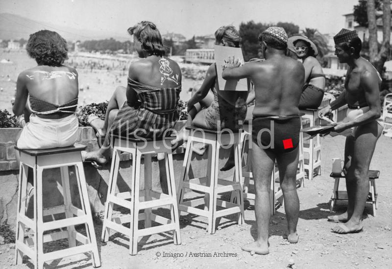Am Strand von Juan-les-Pins bedrucken Männer den Rücken von weiblichen Badegästen. 8. August 1938. Photographie.