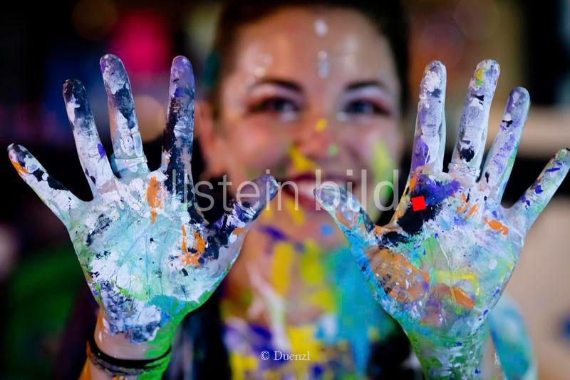 Mit Bodypainting-Farbe befleckte Haende einer Kuenstlerin bei einem Kunst-Event.