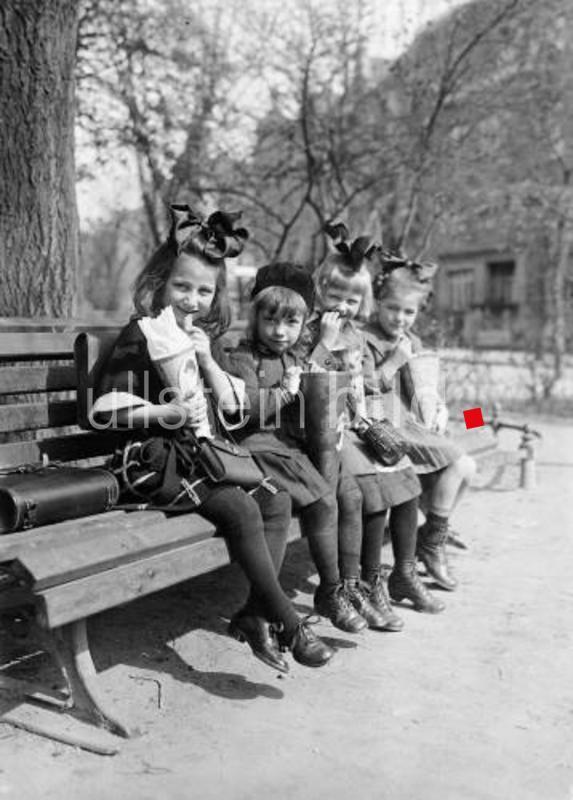 Vier Schülerinnen sitzen am ersten Schultag auf einer Bank in einem Berliner Park und verzehren den Inhalt ihrer Schultüten.