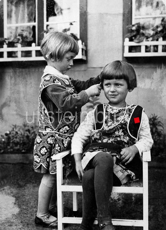 Zwei Kinder spielen Friseur, ca 1920.