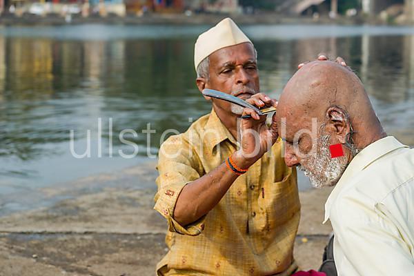 Ein Frisuer rasiert den Kopf eines Pilgerers am Ufer des heiligen Flusses Godwari, Maharashtra, Indien, Asien 2013.