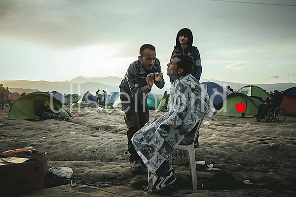 Idomeni Flüchtlingscamp an der griechisch - madzedonischen Grenze. Ein Barbier rasiert einen Flüchtling 2016.