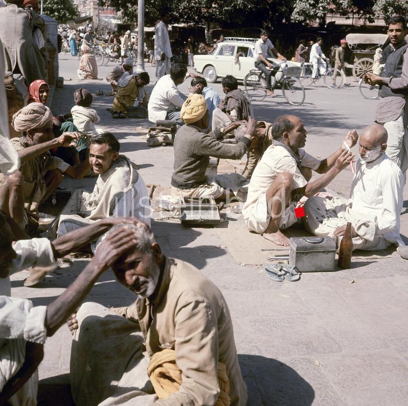 Menschen beim Strassenfriseur in Indien 2008.