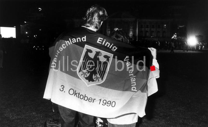 Junges Paar mit der Deutschlandfahne vor dem Reichstagsgebäude