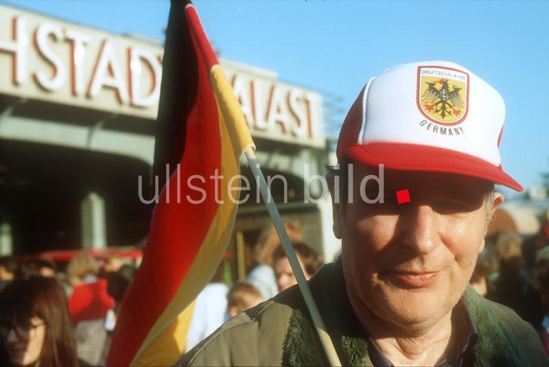 Dia Ehemaliger DDR Bürger mit Deutschlandfahne am Tag der Deutschen Einheit vor dem Friedrichstadtpalast in Berlin