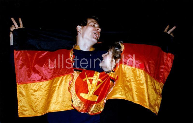 Ein junges Paar tanzt mit einer deutschen Fahne, aus der das Emblem der DDR zur Hälfte herausgetrennt ist.