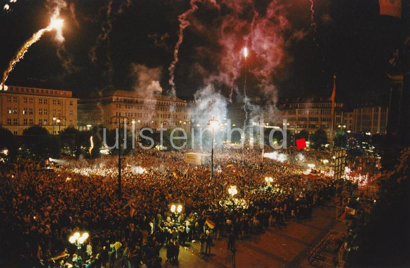 Menschenmassen drängen sich auf dem Hamburger Rathausmarkt, um den offiziellen Tag der Deutschen Einheit zu feiern. Der Platz wird vom Schein eines Feuerwerks erhellt.